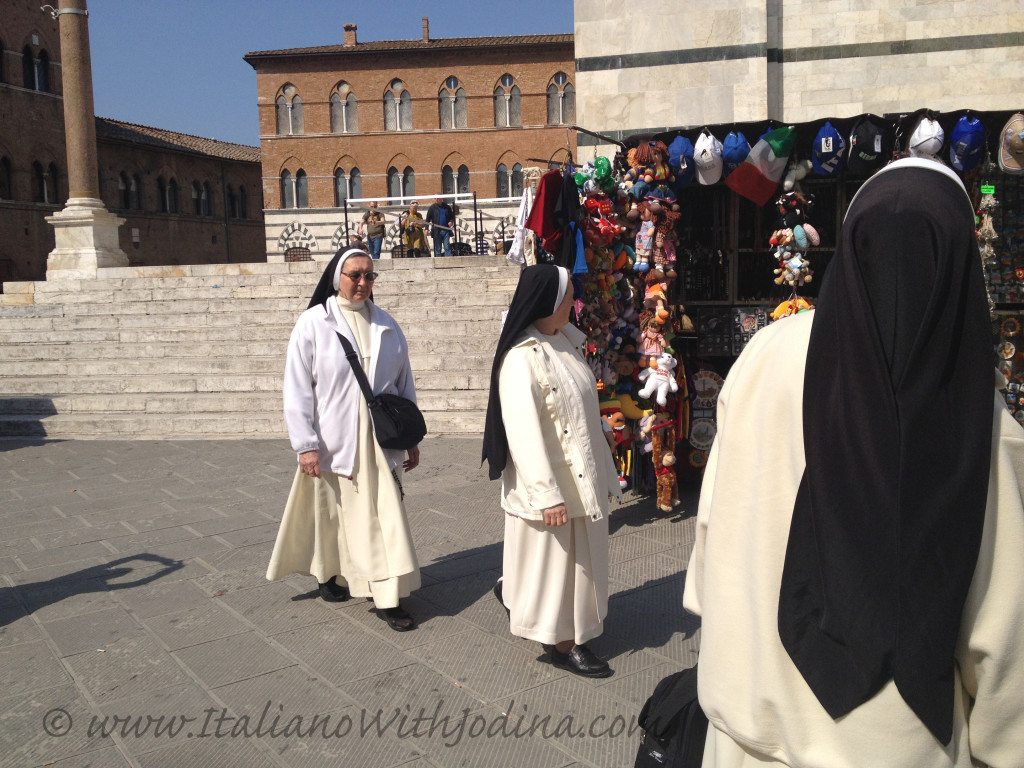 nuns looking at souvenirs piazza duomo siena