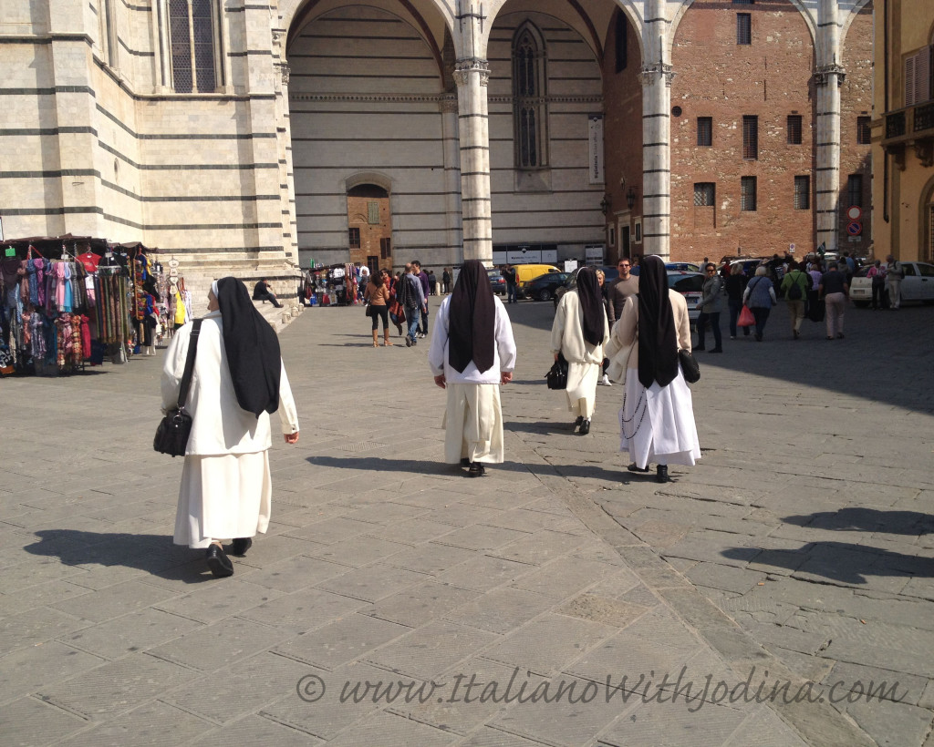 nuns walking into distance piazza del duomo siena